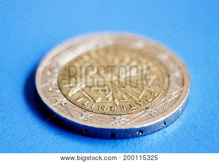 One Euro Coin On Blue Background