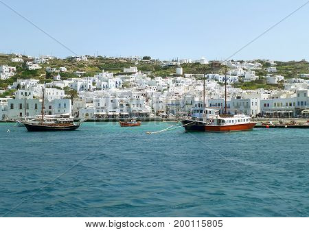 White colored Greek islands architecture on the hillside with vivid color boats at the Mykonos Old Port, Mykonos island of Greece