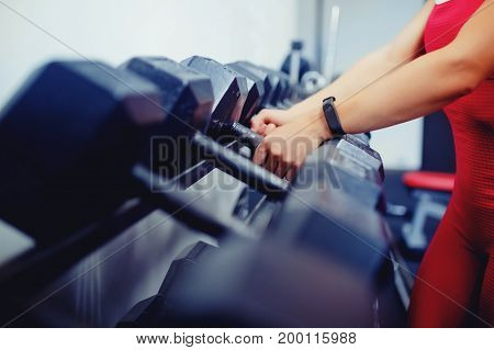 girl takes a hand dumbbells, on her arm is wearing a fitness bracelet, a smart watch in the gym. Blick light, light.