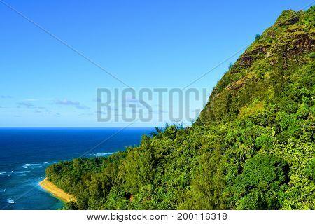 Lush green tropical forest with mountainous terrain surrounding Kee Beach taken at the Napali Coast in Kauai, HI