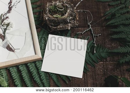 Wedding Invitation Mock-up And Rustic Boutonniere And Wedding Rings In Bird Nest On Wooden  Backgrou
