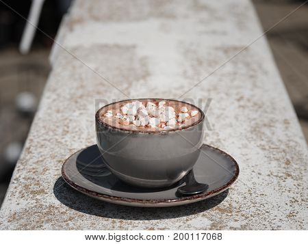 A close-up of an old porcelain mug full of hot chocolate with marshmallows. Sweet cappuccino on a stone background. A cup with a round plate. Copy space. Relaxation, breakfast concept.