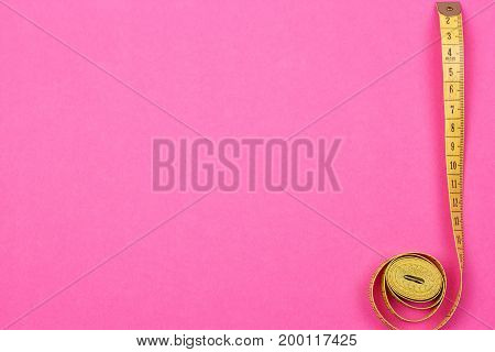 Measuring tape of the tailor on the pink background
