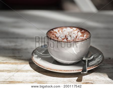 Macro picture of cup with a metal spoon. Tasty cappuccino on a gray wooden table background, close-up. a gray porcelain mug full of sweet cacao drink with white marshmallows.