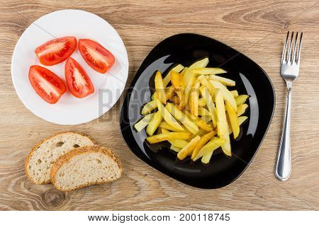 Fried Potatoes In Black Plate, Tomatoes, Bread And Fork