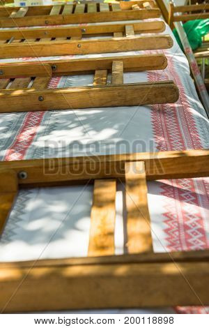 Long table covered with boho style cloth. Folding wooden chairs. Preparation for outdoor summer spring picnic or public fest. Sunlight rays green grass lifestyle.