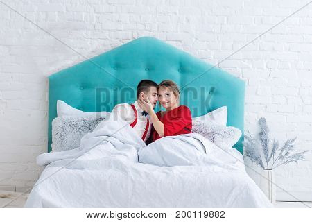 Young adult heterosexual couple lying on bed and looking at each other. Studio shoot