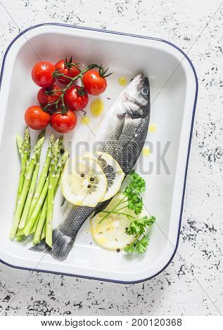 Raw sea bass cherry tomatoes and asparagus in the baking tray. Ingredients for lunch. On a light background top view
