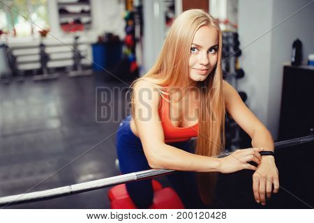 girl is standing in the gym and looks at the frame, on her arm is a fitness bracelet, a smart watch. Concept of technology and sport, pulse measurement, calorie counting. copyspace