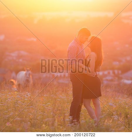 man and girl in love romantic lovers kissing, hugging at sunset, sunrise on the background of mountains and fog, sun, clouds in fiery red, orange colors. Concept wedding, first kiss, love, date. copyspace
