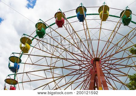 Fragment of a ferris wheel on a cloudy sky background