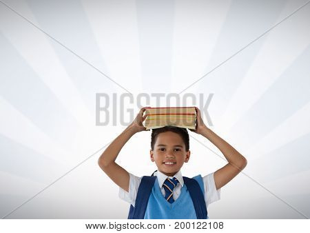 Digital composite of Schoolboy holding books on head with bright background