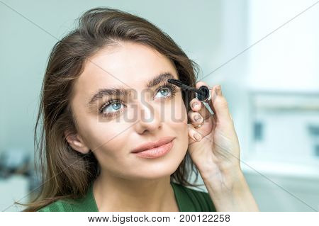 Close up portrait of woman's hand applying beige makeup on eye of pretty girl face using makeup brush. Makeup detail