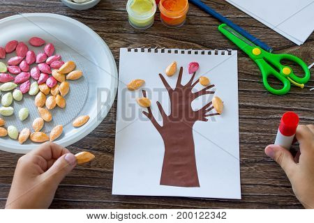 The Child Glues The Details Of The Application. Postcard Autumn Tree With Multi-colored Leaves Of Pu
