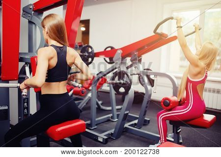 real situation with gym, two girls train on sports simulators.