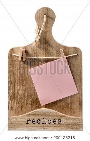 Decorative wooden cutting board with a piece of paper hanging on clothespins for writing prescriptions isolated on white background