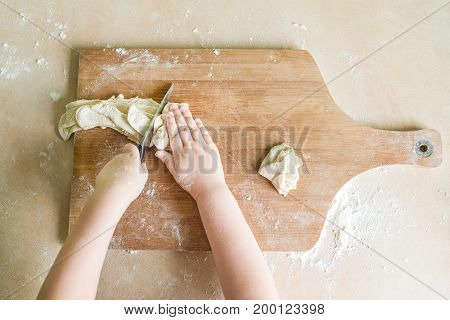 Top view shoot of children's hands cutting raw dough on the wooden board. Learning in kindergarten