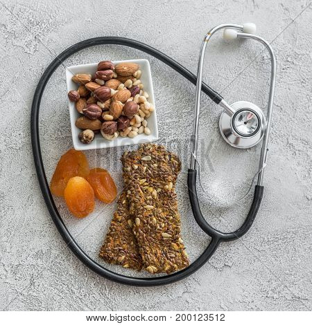 Stethoscope and heart with dried fruits and nuts on a gray background
