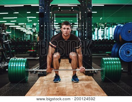 Muscular Man Doing Heavy Deadlift Exercise in gym