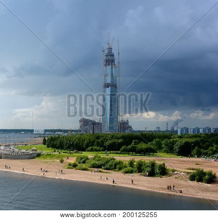 A skyscraper under construction on the seashore under the sky changing from blue to a thunderstorm in St.Peterburg.coub