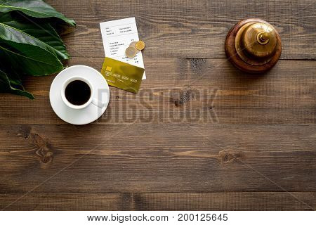 Ask for the bill at cafe. Service bell near coffee and bank card on wooden table top view.