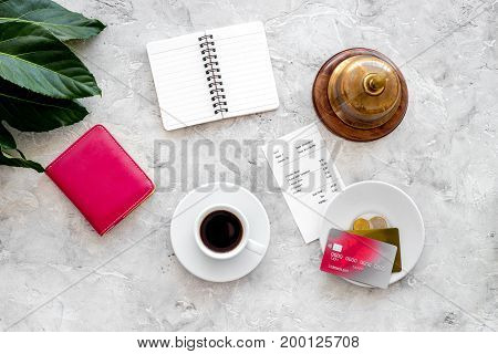 Ask for the bill at cafe. Service bell near coffee, bank card and wallet on grey stone table top view.