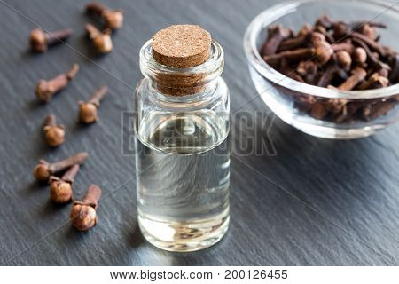 A Bottle Of Clove Essential Oil With Dried Cloves
