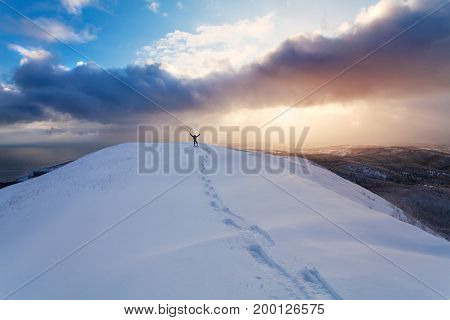 Professional climber on the snowshoeing at top of the rock with his hands up is pleased with the next victory of the ascent and the prints on the snow from his snowshoes. Island Sakhalin.Russia