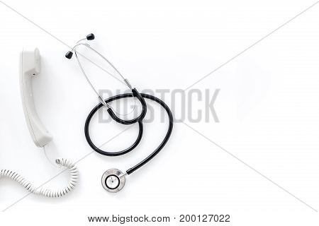 Call doctor. Phone and with stethoscope on white background top view.