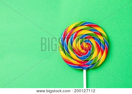 Tasty appetizing Party Accessory Sweet Treat Swirl Candy Lollypop on Bright Green Background Top View Minimalism Fashion Conceptual