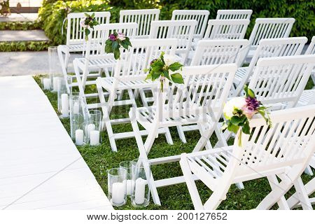 Beautiful wedding set up. Wedding ceremony in the garden. White wooden chairs decorated with flowers and candles standing in rows