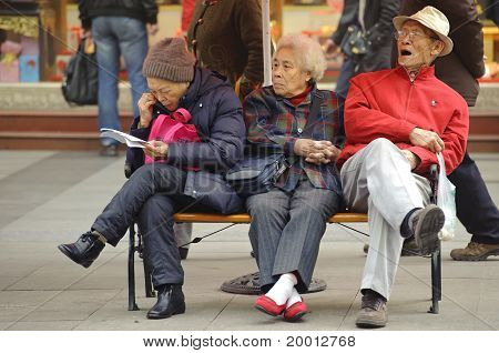A old man and women resting on a chair on a busy pedestrian shopping street