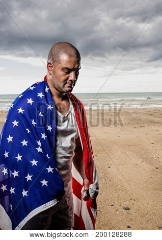 Digital composite of Man holding a USA flag in the beach