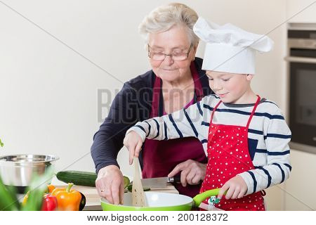 Grandma and grandson cooking together in domestic kitchen
