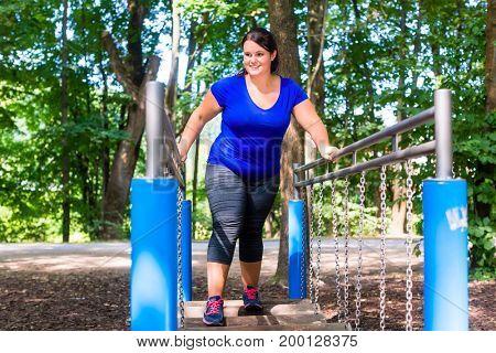 Overweight woman in climbing park doing sport outdoors