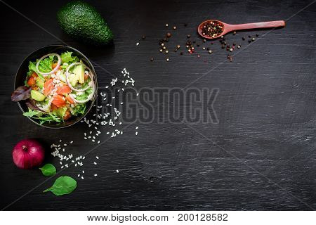 Fresh salad, spicy, avocado mash, pepper, bowl on black background, top view. Vegetarian, healthy, detox food concept. Flat lay, top view.