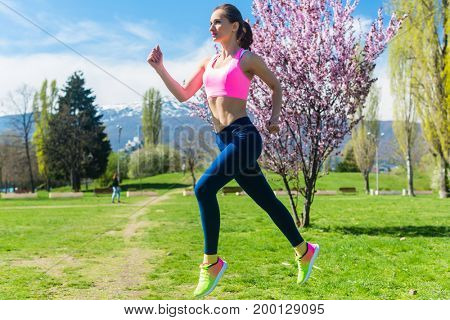 Woman running ot jogging fast for sport on sunny day
