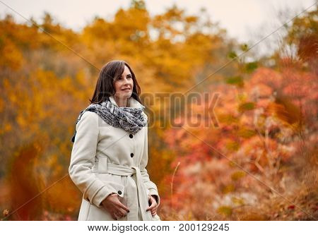 Attractive young woman in warm coat and scarf walking in autumn park