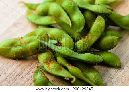 Edamame bean. Boiled immature soybeans in pods on a wooden cutting board with blurred background. Asian traditional food. Macro food photo for cafe, menu, restaurant, design, interior, web, sites.