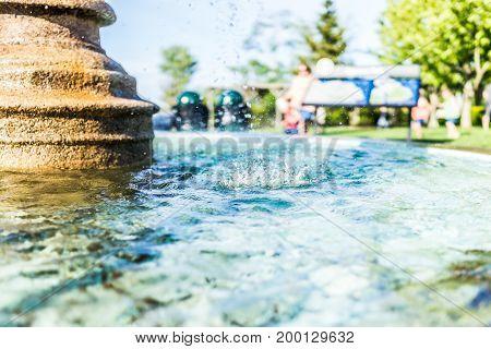 Closeup of splashing water fountain in downtown village park in summer park