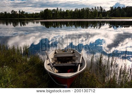 old dirty row boat in forest lake a beautiful summer night in Swedish lapland