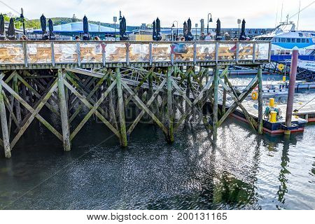 Bar Harbor USA - June 8 2017: Underneath wooden deck dock and waterfront restaurant in downtown village in summer