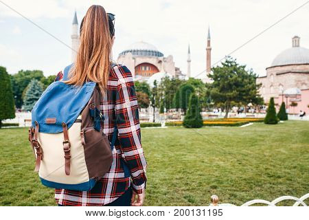 A young traveler girl with a backpack in Sultanahmet Square next to the famous Aya Sofia mosque in Istanbul in Turkey.
