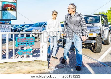 Bar Harbor USA - June 8 2017: Senior couple walking on sidewalk by oceanfront restaurant in downtown village in summer