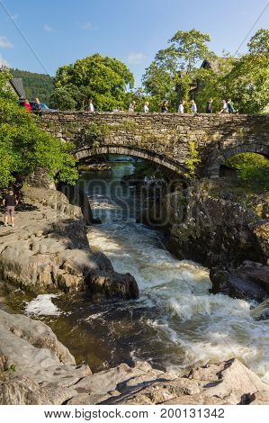 Betws y Coed Wales UK - August 15 2017: The Pont-y-Pair Bridge over the River Llugwy dated from 1475 and is the oldest existing crossing point in the village