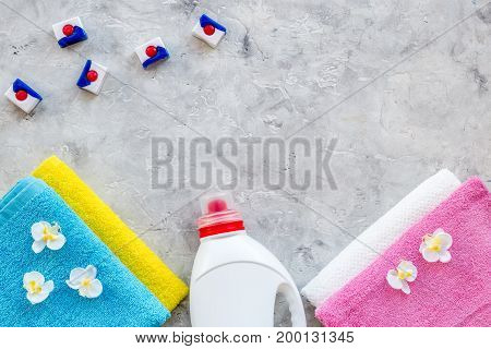 Laundry. Dry and liquid detergents near clean towel on grey stone background top view.