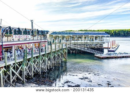Bar Harbor USA - June 8 2017: Wooden deck dock and waterfront lobster restaurant in downtown village in summer