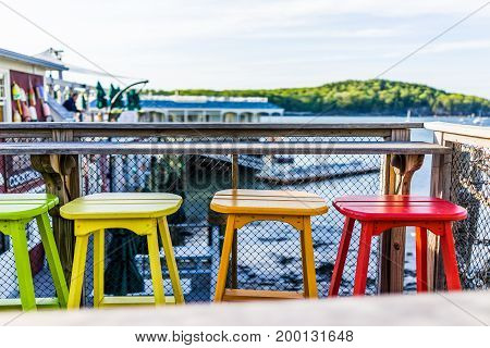 Colorful Vivid Chairs Painted Green, Yellow And Orange On Waterfront Bar Restaurant