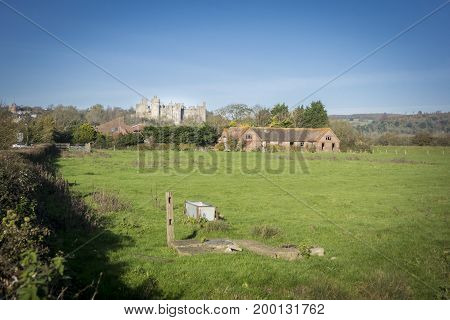 Sussex countryside with a derelict farmhouse and Arundel Castle in the background