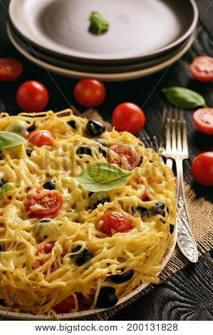 Pasta casserole with tomatoes, olives and cheese.